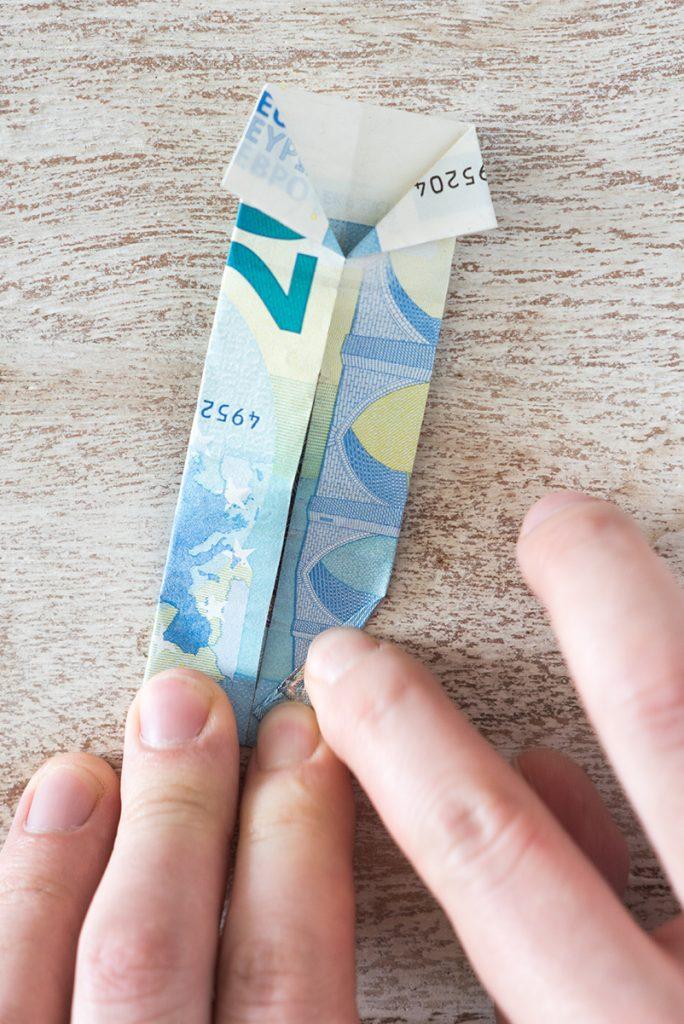 Geldscheinecken zur Mitte knicken